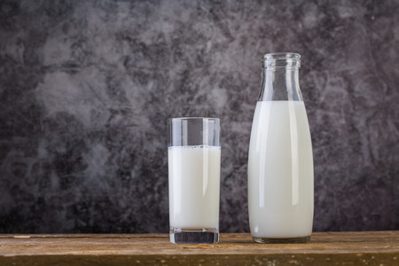 Glass and bottle of fresh milk on wooden table. 写真素材