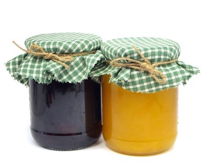 plum jam and honey in glass jars on white background