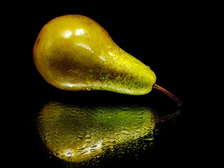 Brown pear on a black background with water drops     photo