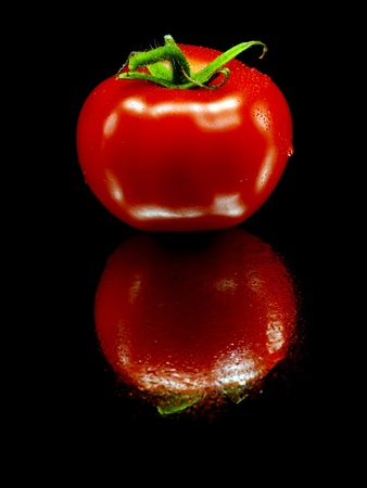 fresh tomatoes on a black background with water drops      photo