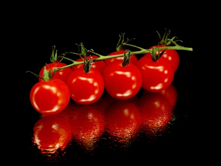 bunch of fresh cherry tomato on a black background with water drops