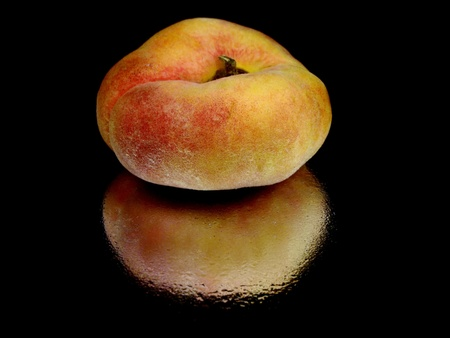 Exotic flat peach on a black background with water drop  photo