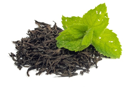 dry black tea leaves and mint on a white background