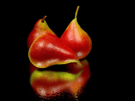 healthier: organic red pear on a black background with water drops