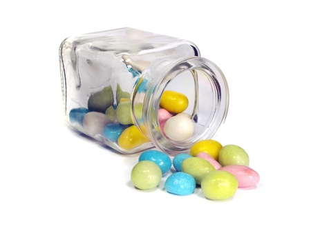 colorful chewy dragees in jar on a white background