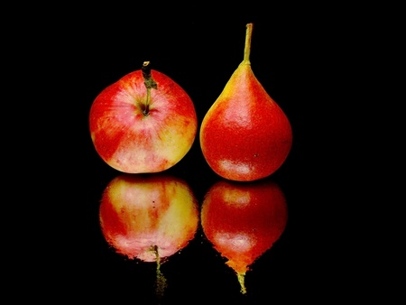organic red pear and apple on a black background with water drops