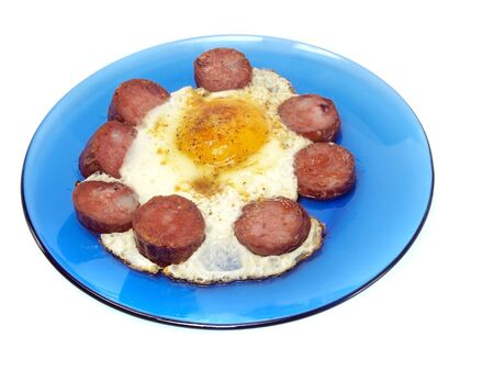 fried sausages and eggs in blue plate on a white background