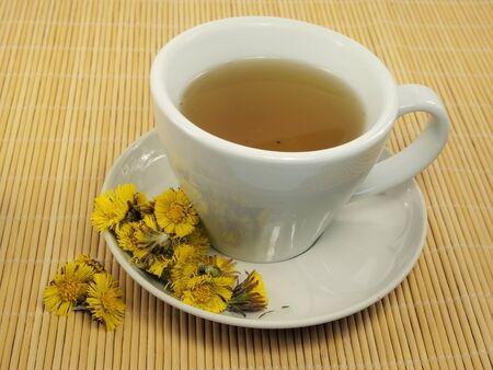 trivet: cup of colts Foot tea cup on a bamboo trivet