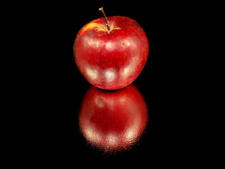 manzana agua: rojo oscuro org�nico de manzana sobre un fondo negro con gotas de agua