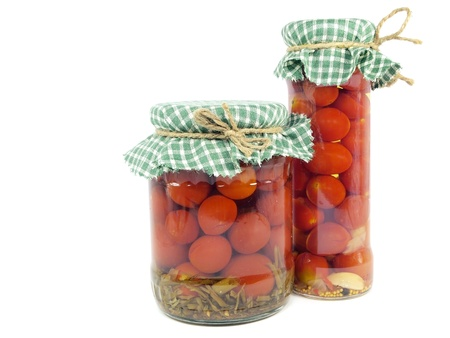 tomatoes canned in glass jar on a white background