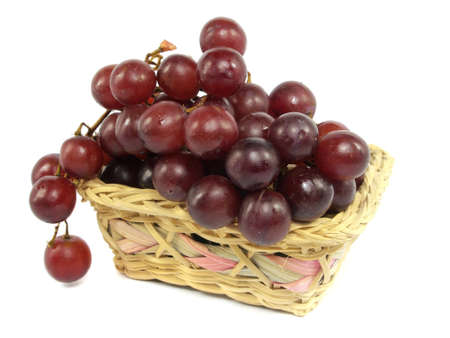 grapes in wicker basket on a white background          photo