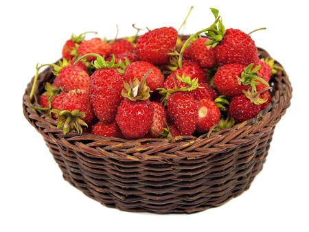 Red wild strawberry in basket on a white background     photo