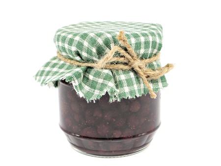 wild strawberry jam in glass jar on white background    photo