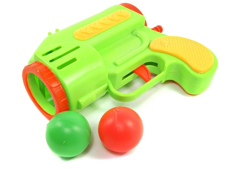 Colorful toy gun with plastic balls on white background   photo
