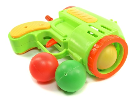 Colorful toy gun with plastic balls on white background   Stock Photo