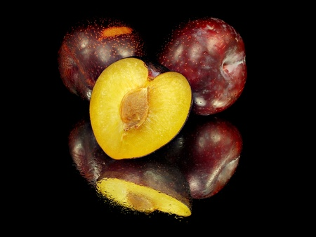 fresh plum on a black background with water drops   Stock Photo