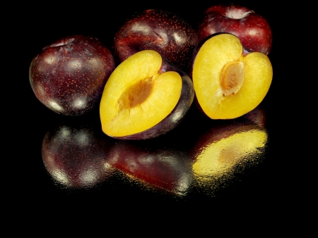 fresh plum on a black background with water drops   photo