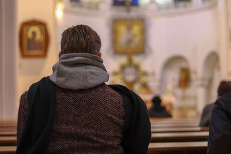 Man in coat from the back close up in Catholic church. Bokeh effect with blur background. Copy space for text. Concept on the theme of faith, religion and church. Men praying. Foto de archivo