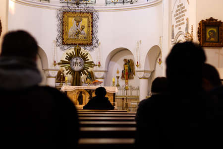 Silhouettes of people sitting in the temple. Service in the catholic church. Dark blurry silhouettes of praying believers. Focus on the background. Copy space for text. Stock Photo