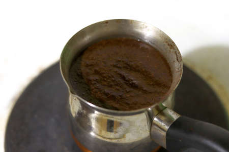 Dark brown coffee in cezve. The process of brewing strong coffee in the morning. Copy space for text.