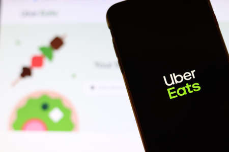 Los Angeles, California, USA - 21 November 2019: Uber Eats logo on phone screen with icon on laptop on blurry background, Illustrative Editorial. Editorial