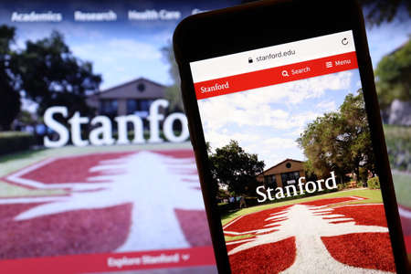 Los Angeles, California, USA - 7 December 2019: Phone screen with Stanford University website page on blurry background with admission page on laptop. Higher education concept, Illustrative Editorial. Editorial