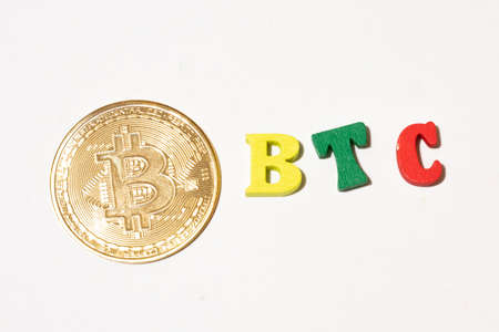 Bitcoin cryptocurrency for illustration, word btc with gold coin made with letterboard.
