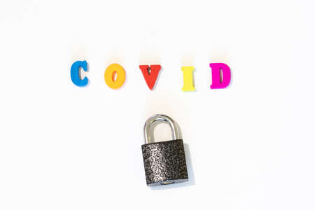 Closed lock with word COVID made with letter board. Concept of country closed borders. Coronavirus is a pandemic virus Stock Photo