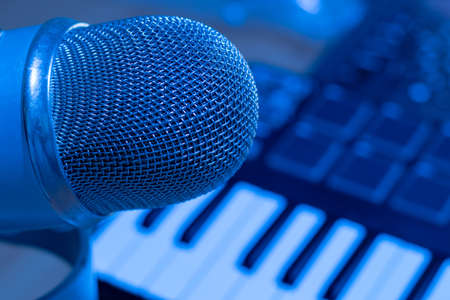 Close up shot microphone in producer musical studio with professional synthesizer.