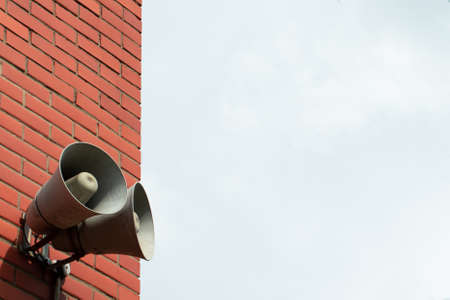 Megaphone on a building on the street. Copy space. Concept of media advertising, announcements, propaganda and alert