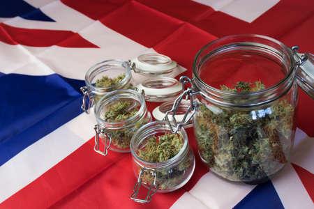 Cannabis buds in jars on UK United Kingdom national flag background. Marijuana business in Great Britain.