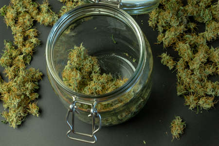 Above top view of cannabis buds in glass jar with marijuana on background.