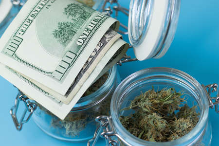 Buying marijuana product from legal shop. Cannabis buds in jar and money on blue background. Foto de archivo