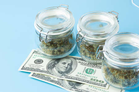 Background with marijuana buds in jars, medical cannabis use in healthcare concept. Weed business industry. Foto de archivo