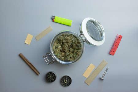 Top view of cannabis smoking stuff. Marijuana and paper on gray background Stock fotó