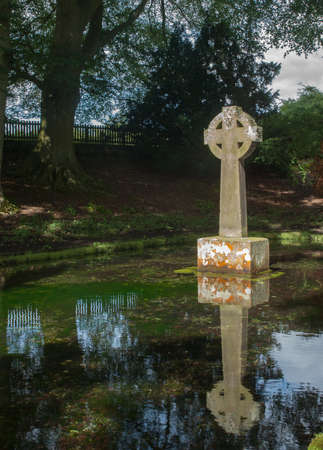 Celtic Cross Reflection In an Ancient  Baptism Pool photo