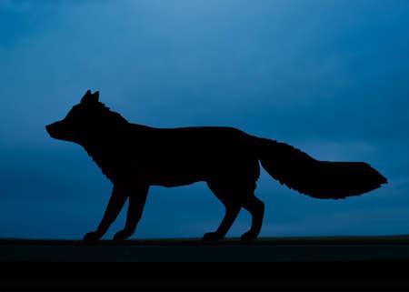 Fox Silhouette shape against a dark blue night sky Stock Photo