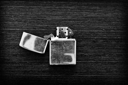 Iron lighter on a dark wooden table in black and white Foto de archivo - 150545764