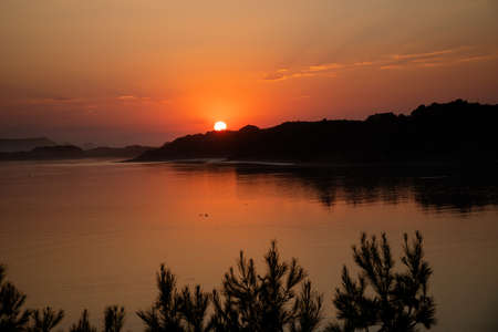 Beautiful orange sunset in the river to the sea with a magic hour light ad calm waters
