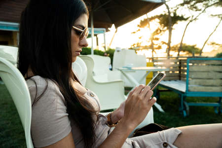 Young pretty woman using her smartphone in a terrace with a beautiful sunset in the background