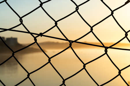 Amazing view of the river to the sea in a beautiful orange sunset through an iron fence Foto de archivo