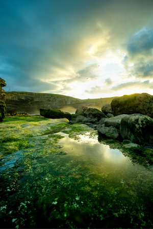 Landscape of a rocky shore with green moss and a nice sunset in Cantabria, Spain