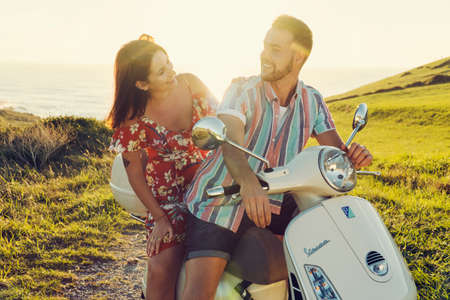 Couple of young friends with fresh clothes, having fun and smiling on a motorcycle in the coast during the sunset light