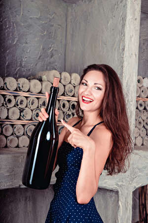 decolletage: beautiful girl in the wine cellar holds a large bottle of wine