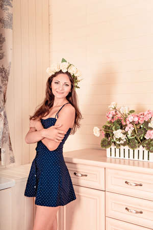 decolletage: girl stands near a white dresser with a wreath on head. there are flowers on the dresser.