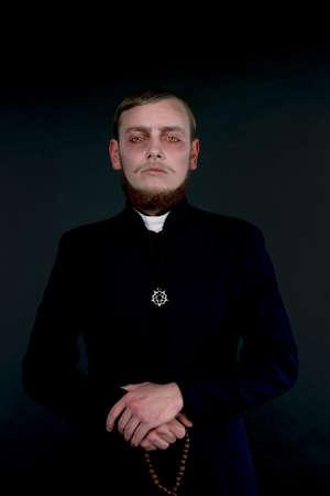 sacerdote: Halloween. Un hombre vestido como el sacerdote católico mal