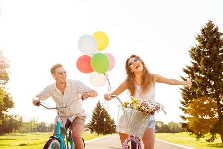 気球および花が付いているバイクに愛のカップル