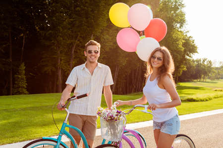 street love: couple in love on bikes with balloons and flowers