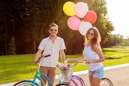 parejas caminando: pareja de enamorados en bicicletas con globos y flores Foto de archivo
