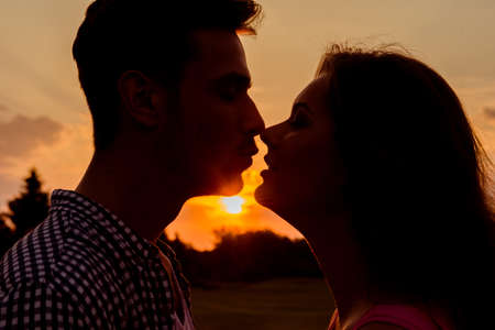 silueta hombre: silueta de la pareja que se besa en la puesta del sol Foto de archivo